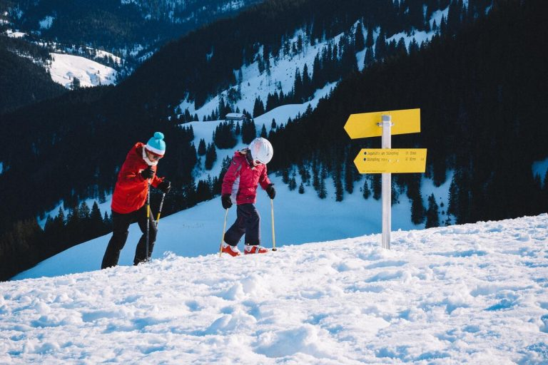 man and kid walking on ski area
